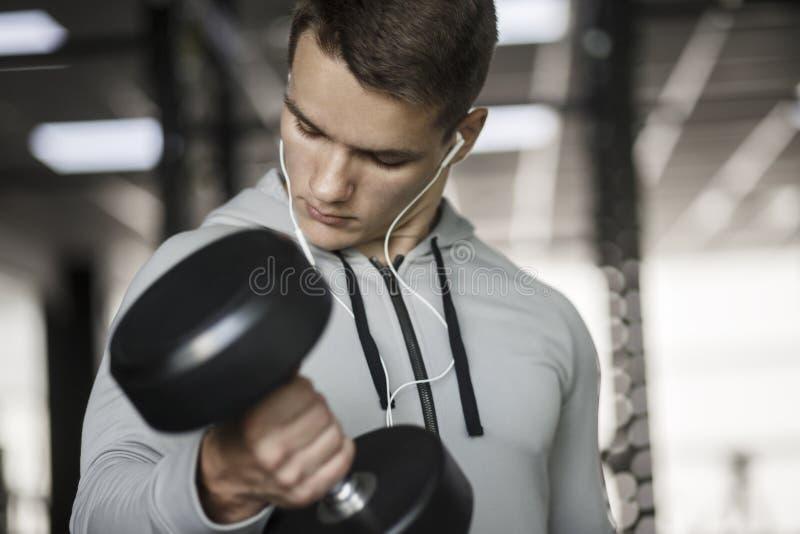 Individuo muscular del culturista que hace ejercicios con pesas de gimnasia en gimnasio imagenes de archivo