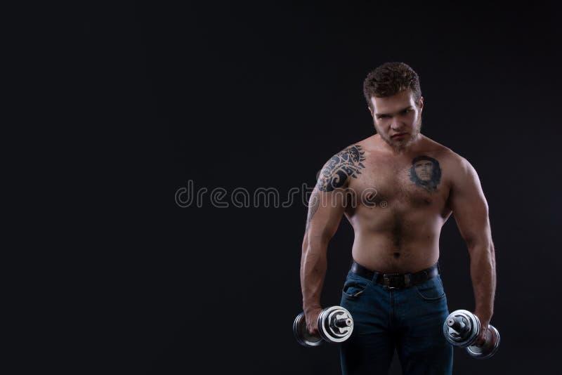 Individuo muscular del culturista que hace ejercicios con pesas de gimnasia sobre fondo negro foto de archivo
