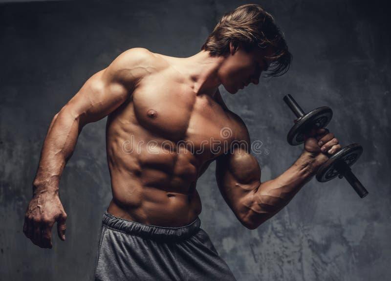 Individuo muscular descamisado que hace ejercicio del bíceps imagenes de archivo