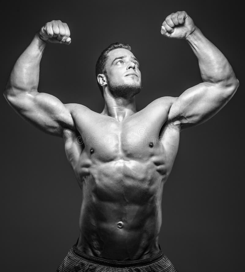 Individuo muscular impresionante que presenta en estudio fotografía de archivo libre de regalías