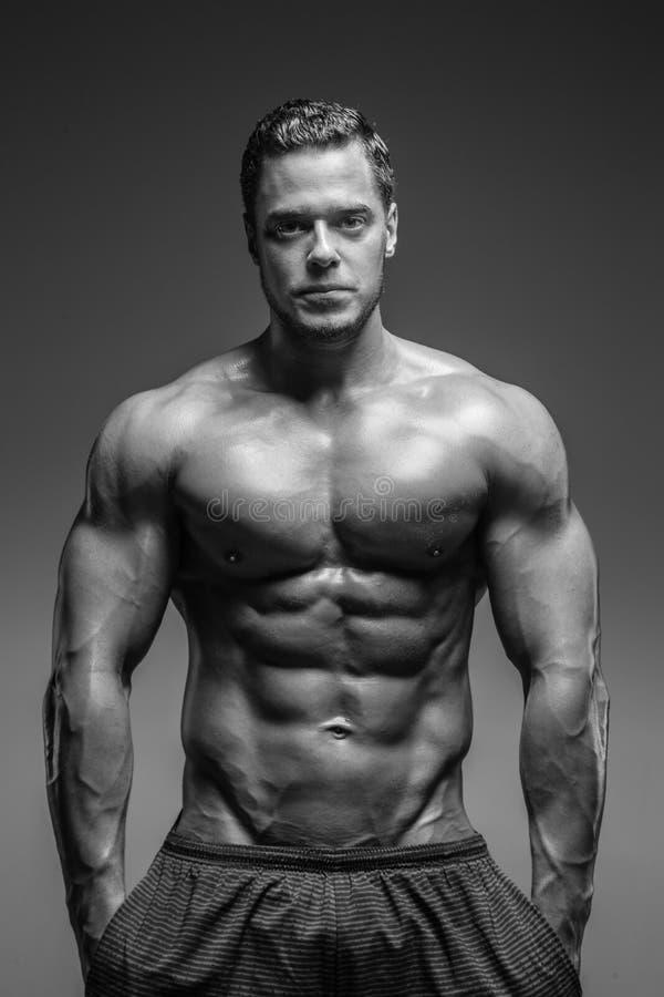 Individuo muscular impresionante que presenta en estudio imágenes de archivo libres de regalías
