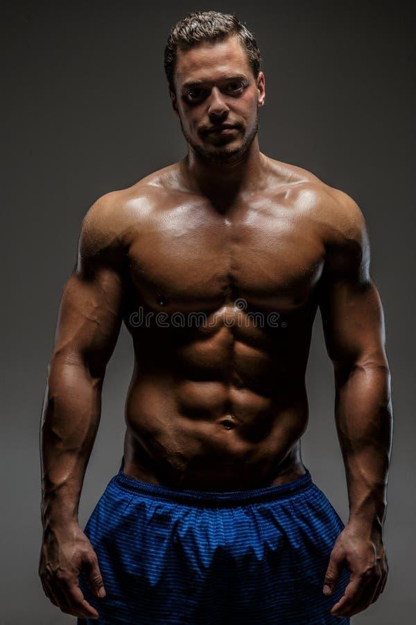 Individuo muscular impresionante que presenta en estudio fotos de archivo