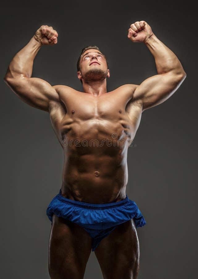 Individuo muscular impresionante que presenta en estudio imagen de archivo libre de regalías