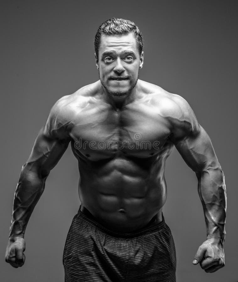 Individuo muscular impresionante que presenta en estudio fotografía de archivo