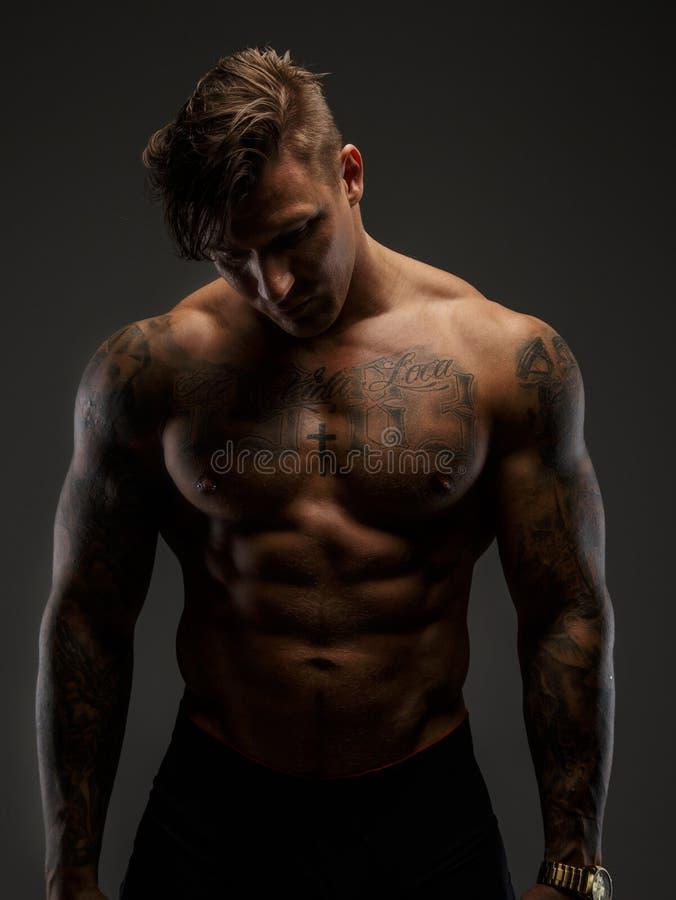 Individuo muscular que mira abajo foto de archivo libre de regalías