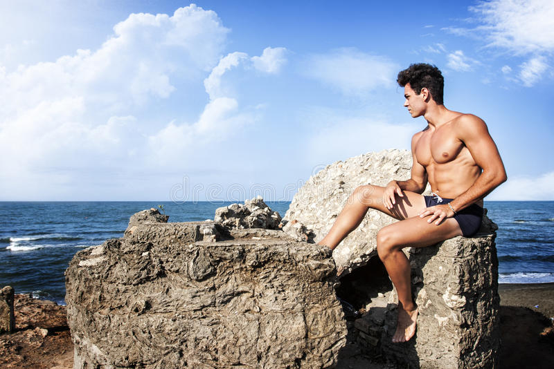 Individuo muscular que se sienta en la roca, mar Mediterráneo fotografía de archivo libre de regalías