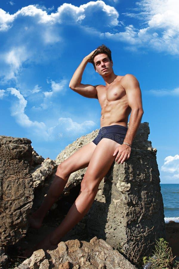 Individuo muscular que se sienta en la roca, mar Mediterráneo imagen de archivo libre de regalías