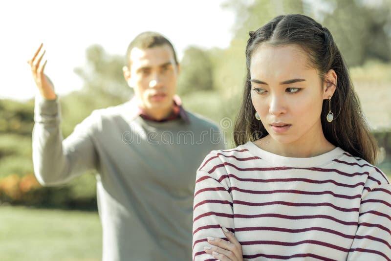 Individuo oscuro-cabelludo activo que tiene problemas en relaciones con la muchacha bonita imágenes de archivo libres de regalías