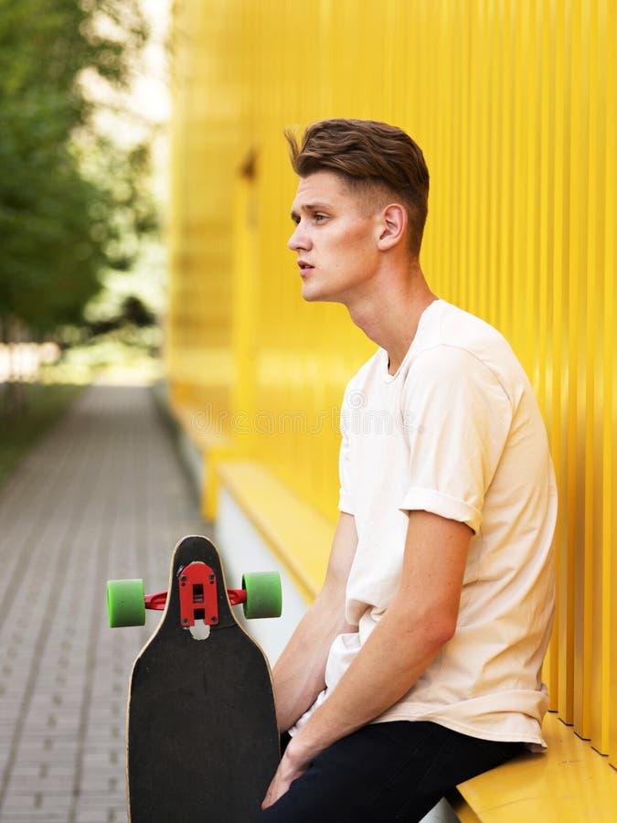 Individuo pensativo con un monopatín en un fondo borroso de la calle El inclinarse adolescente casual en una pared amarilla Conce fotos de archivo libres de regalías