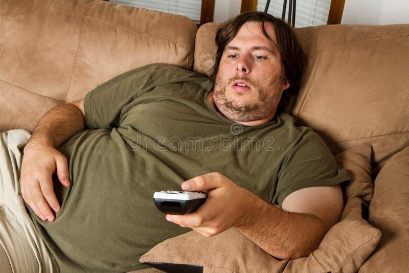 Individuo perezoso gordo en el sofá foto de archivo