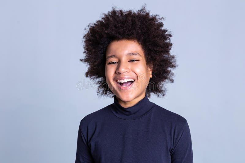 Individuo positivo apuesto de risa que permanece en fondo gris foto de archivo