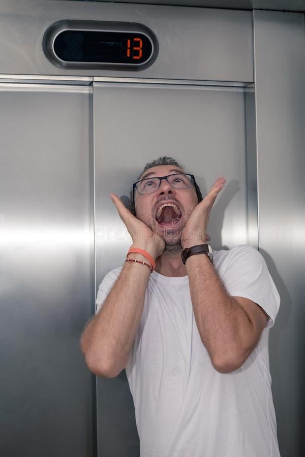 Individuo preocupante en el piso trece en elevador Concepto de la mala suerte fotografía de archivo