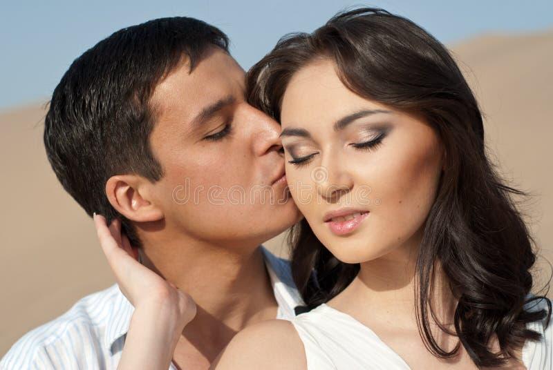 Individuo que besa a una muchacha hermosa fotografía de archivo