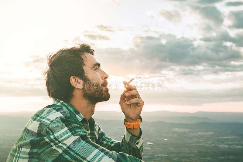Individuo que fuma un cigarrillo Casual vestido individuo y con una barba foto de archivo