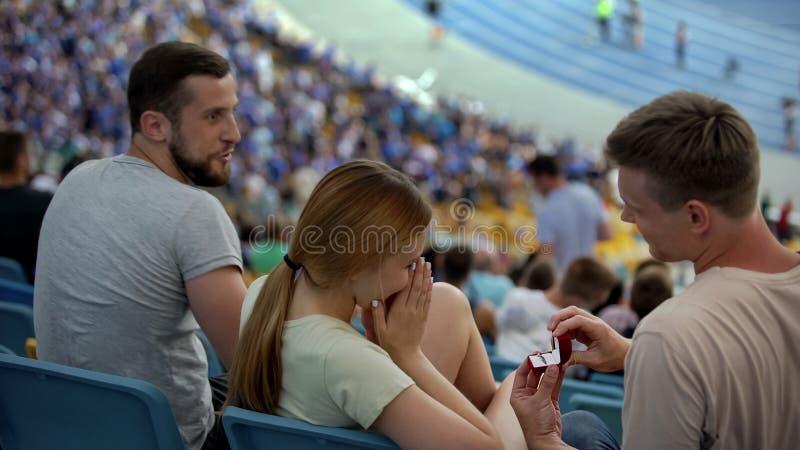 Individuo que hace oferta a la novia en el estadio durante el partido de fútbol, sorpresa fotos de archivo libres de regalías