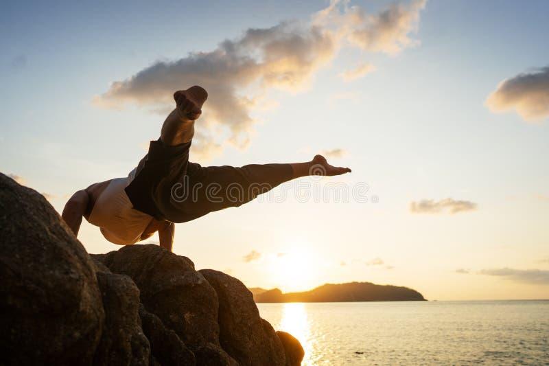 Individuo que hace yoga acrobática en la puesta del sol por el mar fotos de archivo