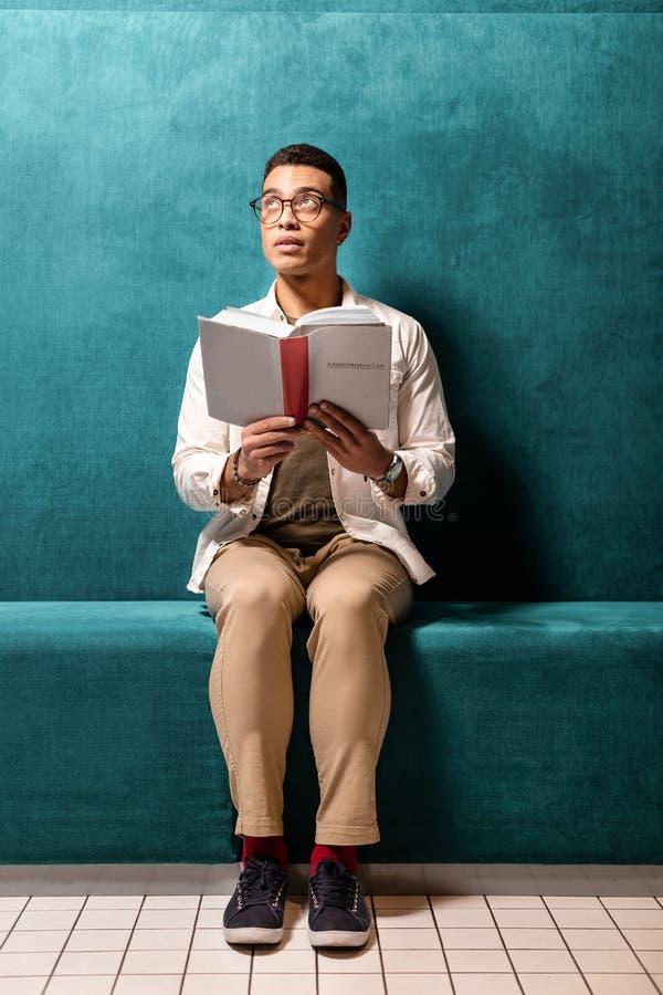Individuo que se sienta en la sala de espera y esperar la llegada del amigo mientras que escucha los avisos imagen de archivo