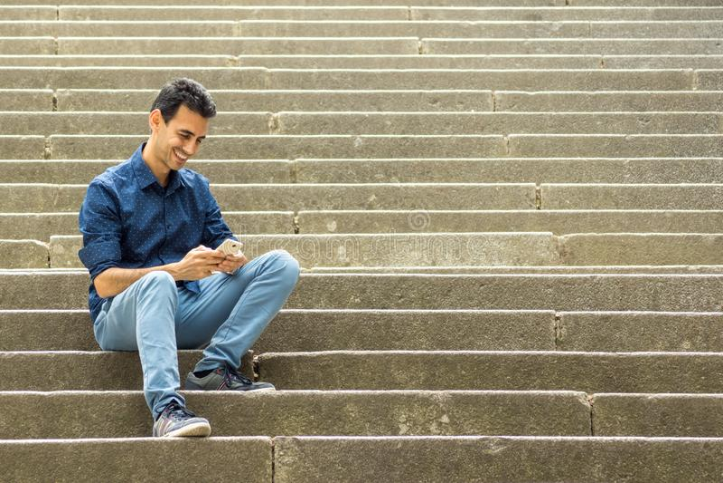 Individuo que se sienta en las escaleras con smartphone imagen de archivo
