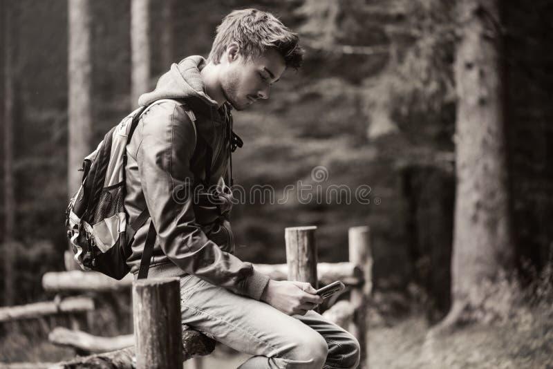 Individuo que se sienta en una cerca y mandar un SMS foto de archivo