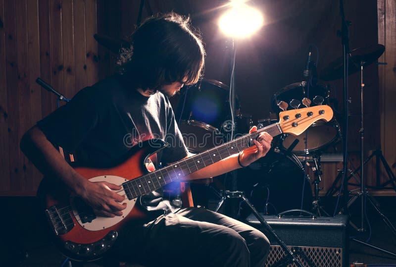 Individuo que toca la guitarra baja imagen de archivo libre de regalías