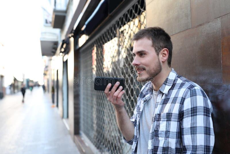 Individuo que usa el reconocimiento vocal en el teléfono elegante afuera fotografía de archivo libre de regalías
