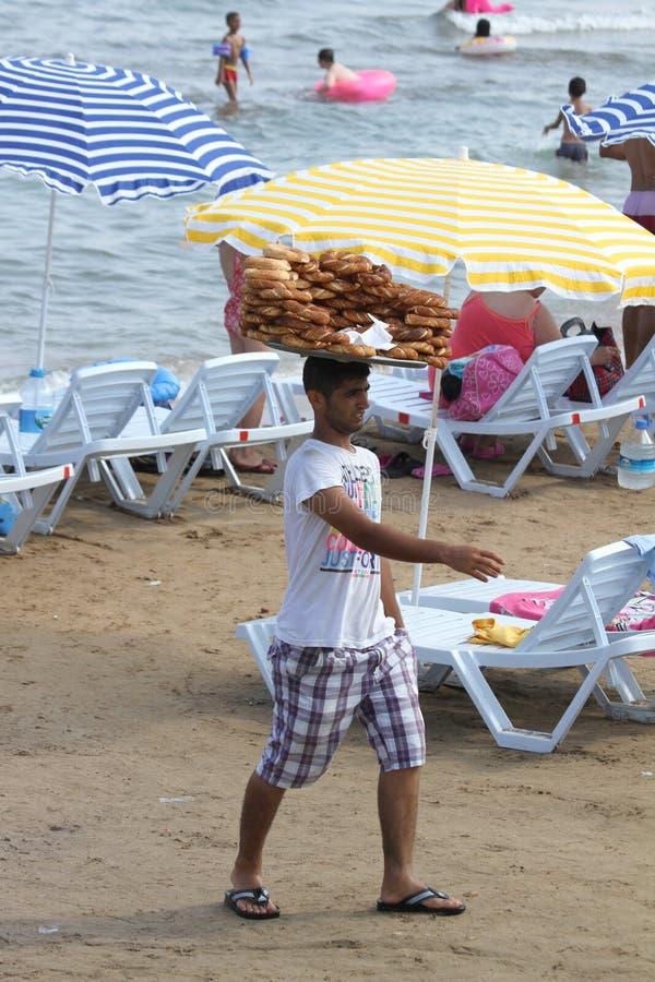 Individuo que vende el panecillo turco Simit en la playa de Kizkalesi foto de archivo libre de regalías