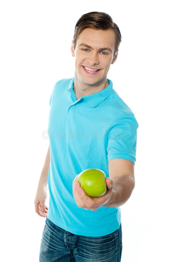 Individuo sano apuesto que ofrece una manzana verde imagen de archivo