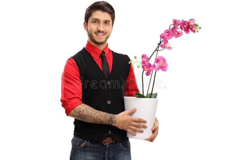 Individuo tatuado que sostiene una flor de la orquídea en un pote fotos de archivo libres de regalías