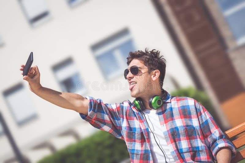 Individuo urbano con los auriculares que toman el selfie al aire libre fotos de archivo