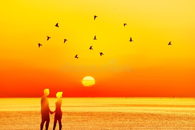 Individuo y muchacha de la silueta en puesta del sol fotografía de archivo