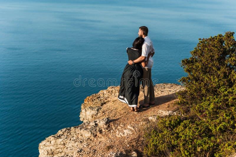 Individuo y muchacha en el mar que abraza al borde del acantilado fotos de archivo libres de regalías