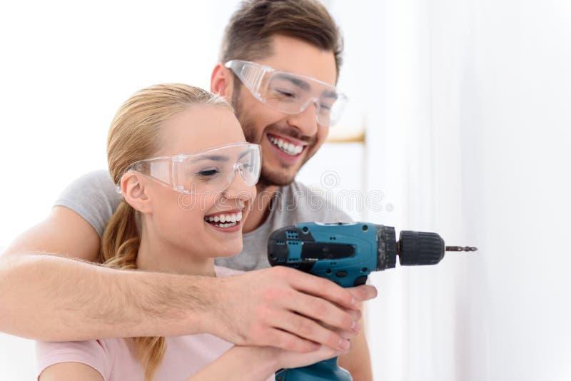 Individuo y muchacha sonrientes que hacen el agujero usando el taladro foto de archivo libre de regalías
