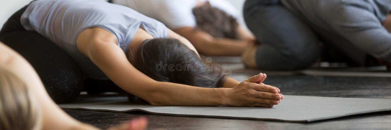 Individuos deportivos de las muchachas que practican el ejercicio del niño que hace actitud de la yoga de Balasana imágenes de archivo libres de regalías