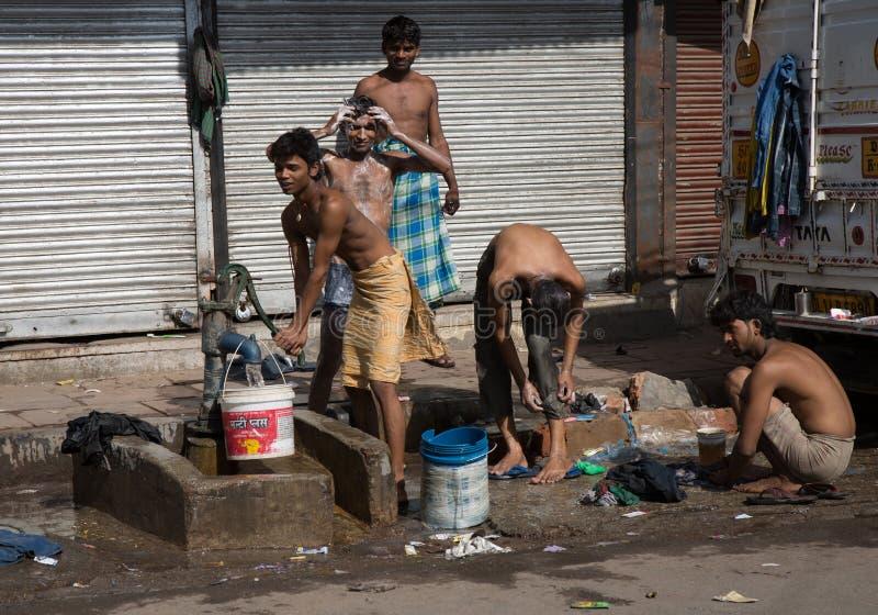 Individuos indios jovenes que se lavan en el camino fotos de archivo