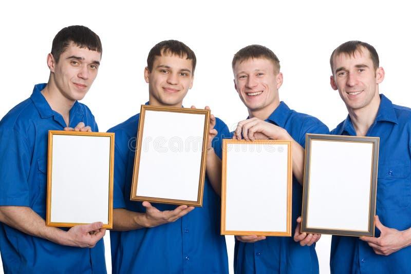 Individuos jovenes que llevan a cabo el marco vacío imagen de archivo