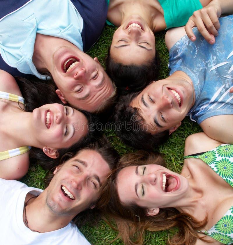 Individuos jovenes y muchachas que mienten en la hierba que mira para arriba imagen de archivo