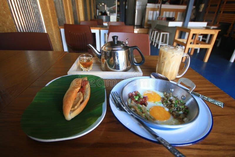 Indochina Pan-briet Ei mit Belägen mit Stangenbrotbrotsandwich mit Käse, Schinken auf frischer grüner Banane und Eiskaffee, Tee lizenzfreie stockfotos