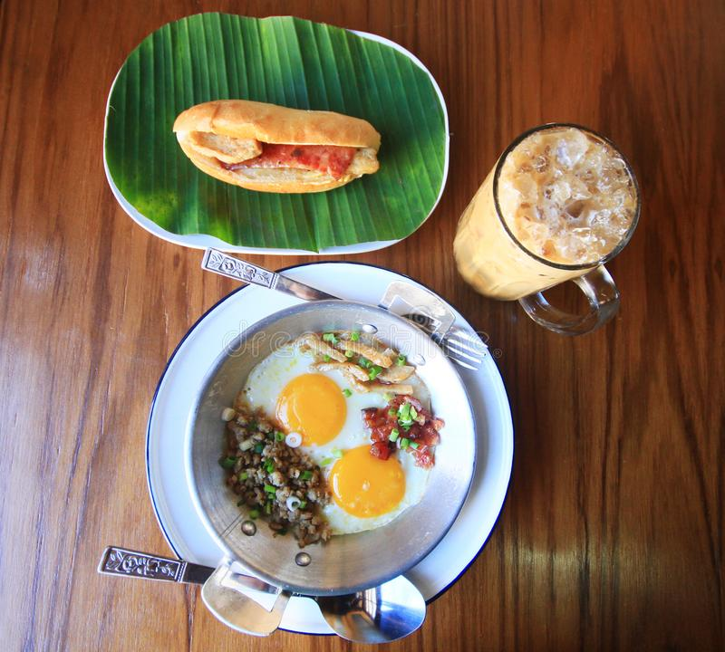 Indochina pan-fried egg with toppings with Baguette bread sandwich with cheese, ham on fresh Green banana leaf and ice coffee stock photography