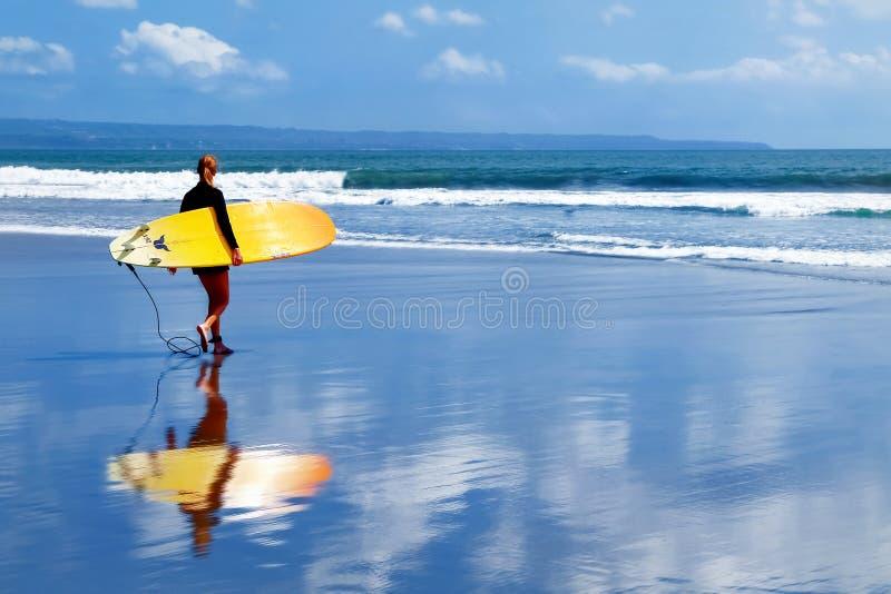 Indonésia, ilha de Bali, Kuta - 10 de outubro de 2017: Surfista da menina com uma prancha que anda ao longo da praia Escola de su foto de stock royalty free