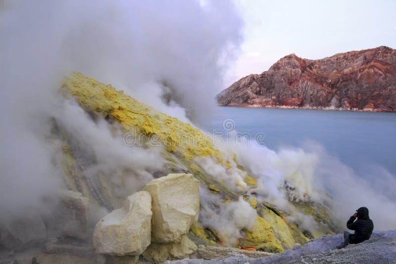 Indonésia, Java, 27 Desember 2015 Pessoa no nascer do sol na cratera de um vulcão ativo de Ijen imagem de stock royalty free