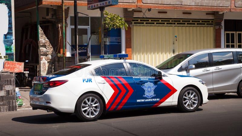 Indonesië - de Lokale politiewagen verstrekt veiligheid in Jalan Penataran Agung, Bali stock afbeelding