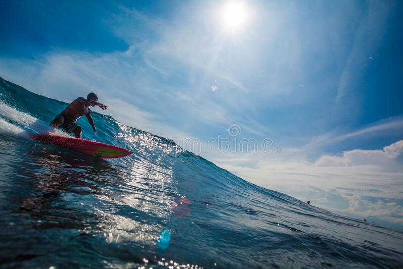 Indonesia, Bali, July 13 2016: A male surfer riding big blue oce stock photography