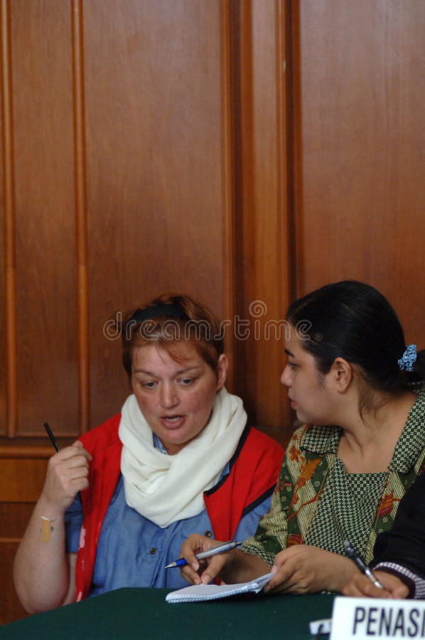 Indonesia Britain Drug Trial. British national Andrea Waldeck (L) is escorted by a court official prior to her trial in Surabaya on October 1, 2013. Waldeck is royalty free stock photos