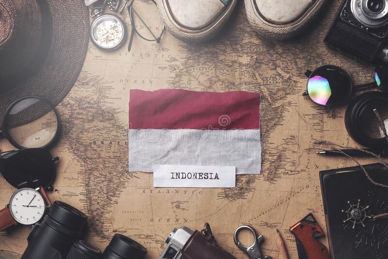 Indonesia Flag Between Traveler`s Accessories on Old Vintage Map. Overhead Shot.  stock image
