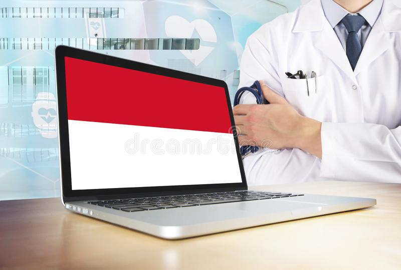 Indonesia healthcare system in tech theme. Indonesian flag on computer screen. Doctor standing with stethoscope in hospital. Cryptocurrency and Blockchain stock photo