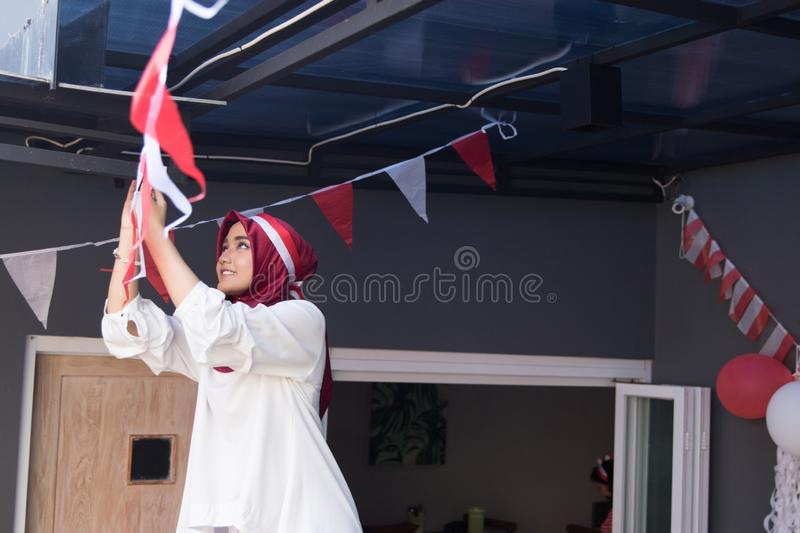 Indonesia independence day decorating house. Happy asian muslim woman preparing for indonesia independence day decorating her house stock images