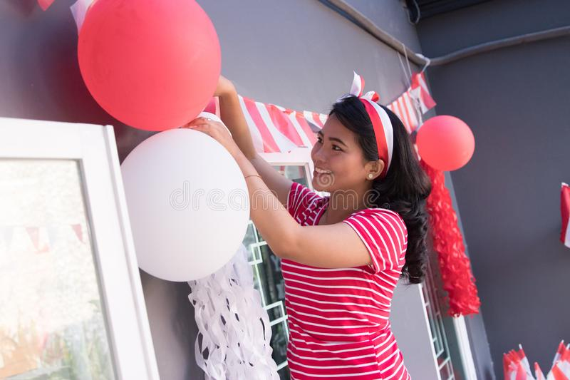 Indonesia independence day decoration. Happy asian woman preparing for indonesia independence day decorating her house stock images