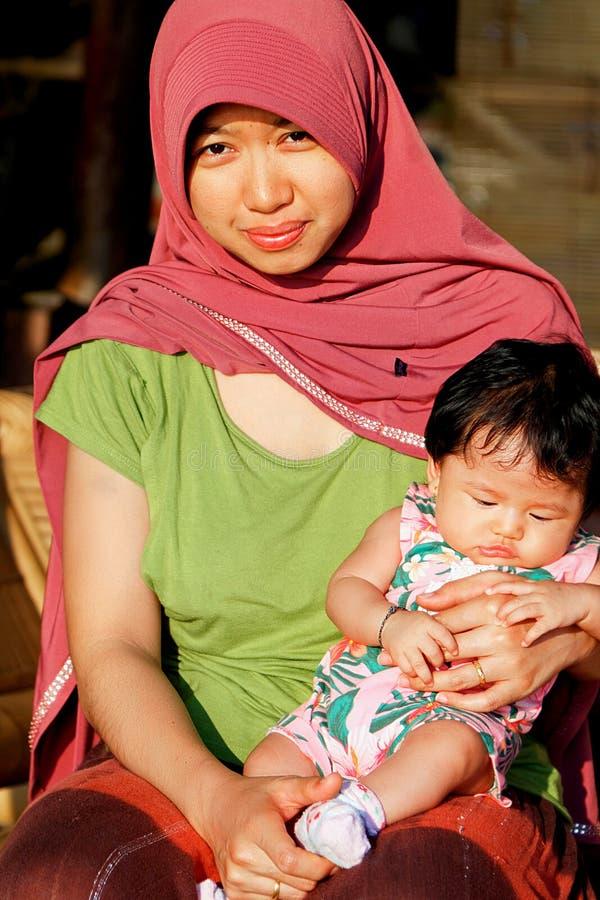 Indonesia, isla de Java - 19 de septiembre de 2017: Una mujer musulmán local con una reclinación del niño al aire libre foto de archivo libre de regalías