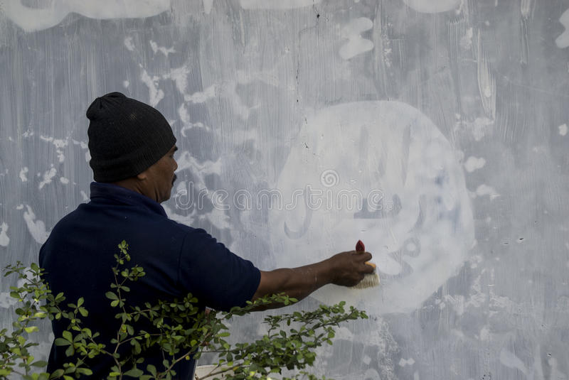INDONESIA ISLAMIC STATE WAR. Government officials erase an Islamic State graffiti on a street side wall at Solo, Java, Indonesia. Indonesian President Joko stock images
