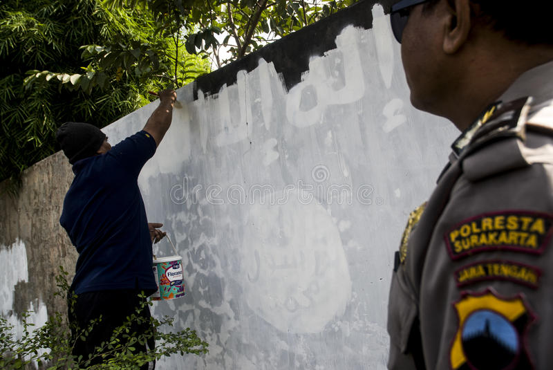 INDONESIA ISLAMIC STATE WAR. Government officials erase an Islamic State graffiti on a street side wall at Solo, Java, Indonesia. Indonesian President Joko royalty free stock photos
